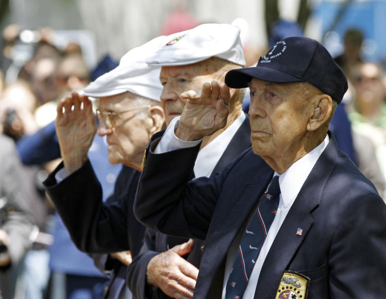 Surviving Doolittle Raider Richard E. Cole, right, salutes during the singing of the national anthem at a memorial service for the the 70th anniversary of the Doolittle raid on Tokyo at the National Museum of the United States Air Force in Dayton, Ohio Wednesday, April 18, 2012. Four survivors took part in the ceremonies including David Thatcher, second from right, Thomas C. Griffin, left, and Edward E. Saylor, not seen. (AP Photo/Mark Duncan)