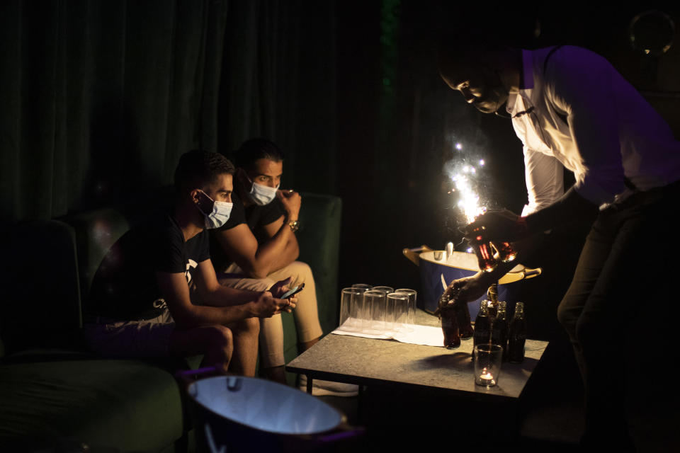 People wearing face masks to prevent the spread of coronavirus gather in a discotheque in Madrid, Spain, early Saturday, July 25, 2020. Nightlife is becoming the new target of Spanish authorities attempting to contain a spike in coronavirus infections since the country ended a lockdown. The Catalonia regional government has shut nightlife venues in Barcelona, and on Friday officials in Madrid said they were considering a similar step. (AP Photo/Manu Fernandez)