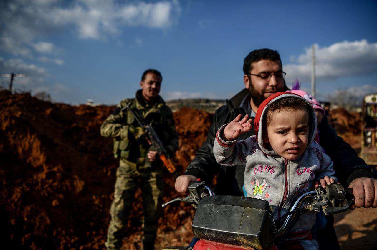 <p>A Turkish-backed Syrian rebel fighter stands guard at a checkpoint as a family passes on motobike in the Syrian town of Azaz on a road leading to Afrin, on Feb. 1, 2018. (Photo: Ozan Kose/AFP/Getty Images) </p>