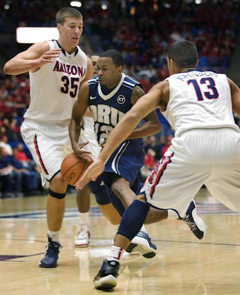 Oral Roberts' D.J. Jackson (12) loses the ball driving between Arizona's Kaleb Tarczewski (35) and Nick Johnson (13) during the first half of an NCAA college basketball game at McKale Center in Tucson, Ariz., Tuesday, Dec. 18, 2012. (AP Photo/Wily Low)