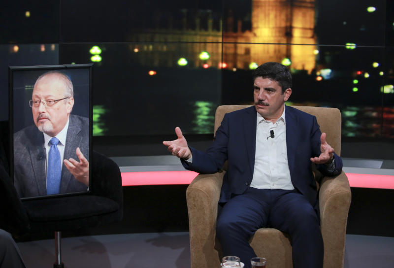 Yasin Aktay, an advisor to Turkey's President Recep Tayyip Erdogan and a good friend sits next to an empty chair with a picture of Saudi writer Jamal Khashoggi placed on it, speaks during a live television program for London-based TV station al-Hewar, in Istanbul, late Thursday, Oct. 11, 2018. Khashoggi was supposed to appear on the show. The TV presenter Azzam Tamimi, a prominent Palestinian and a good friend of Khashoggi, told The Associated Press that the program was planned to discuss his new projects, his books and other issues.(AP Photo/Mucahid Yapici)