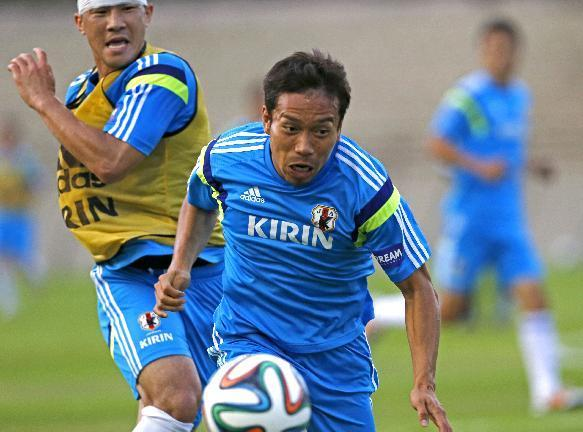 In this June 8, 2014 photo, Japan's Yuto Nagatomo, center, controls the ball during a training session in Sorocaba, Brazil. Nagatomo's unprepossessing exterior hides a player who is built like a tank and runs like a racehorse, and could be Japan's secret weapon at the World Cup. (AP Photo/Shuji Kajiyama)
