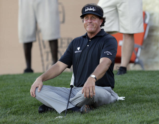 Phil Mickelson sits on the grass as watches his playing partners finish the 16th hole during the second round of the Texas Open golf tournament, Friday, March 28, 2014, in San Antonio. (AP Photo/Eric Gay)