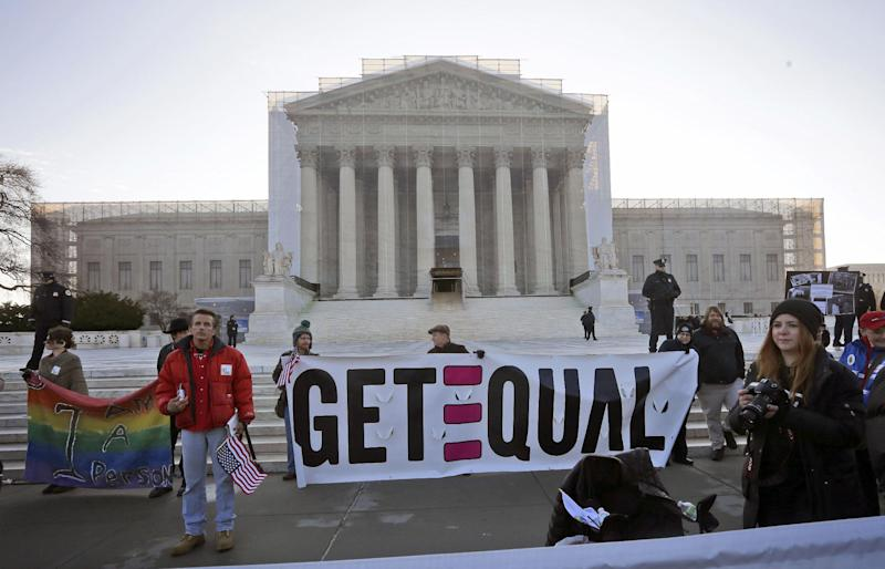 Demonstrators stand outside the Supreme Court in Washington, Tuesday, March 26, 2013, where the court will hear arguments on California's voter approved ban on same-sex marriage, Proposition 8. (AP Photo/Pablo Martinez Monsivais)