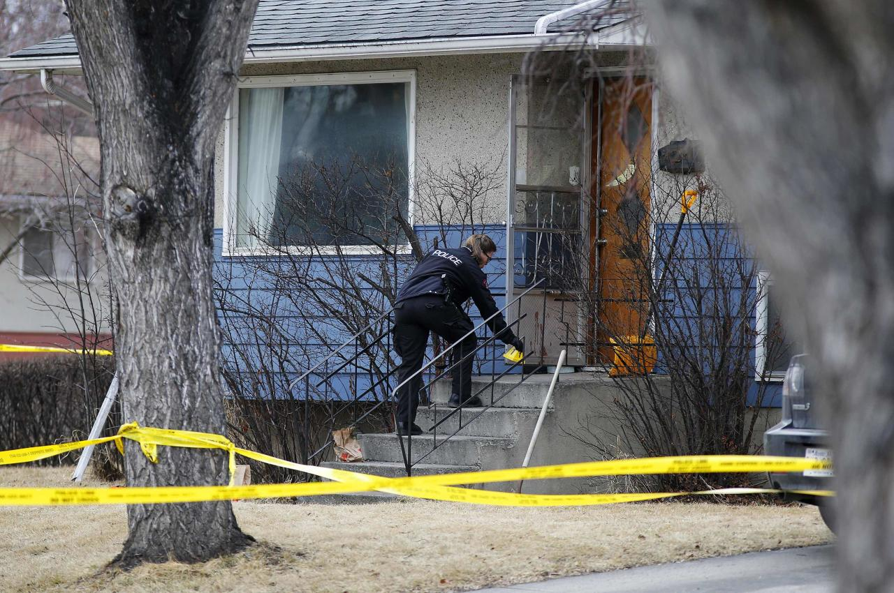 A police officer puts down evidence markers at a house where five people were stabbed in the early morning hours in Calgary, Alberta, April 15, 2014. Three people died on the scene of the crime while two others died in hospital, according to local media. The police have one person in custody. REUTERS/Todd Korol (CANADA - Tags: CRIME LAW)