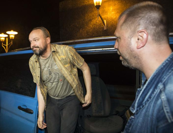 """An unidentified member of OSCE Special Monitoring Mission in Ukraine walks out of a vehicle next to Alexander Borodai (R), Prime Minister of the self proclaimed """"Donetsk People's Republic"""" , on arrival at the city of Donetsk after being released from captivity, June 27, 2014. REUTERS/Shamil Zhumatov (UKRAINE - Tags: POLITICS CIVIL UNREST)"""