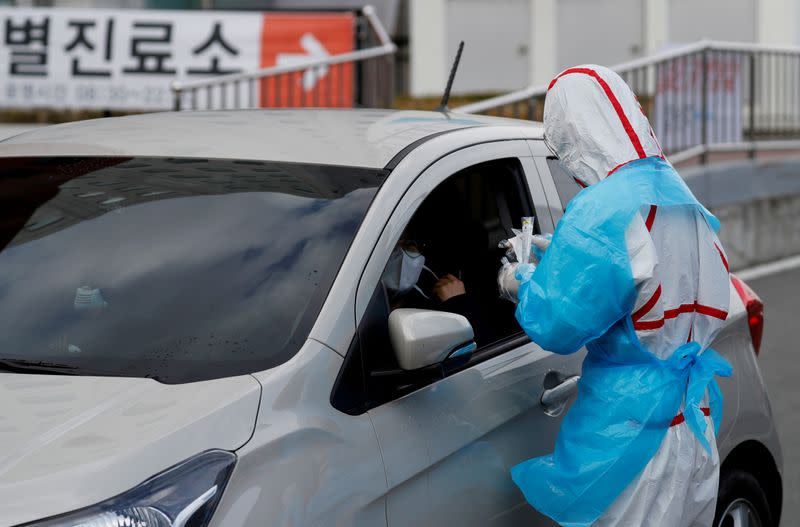 FILE PHOTO: A medical staff member in protective gear prepares to take samples from a visitor at a 'drive-thru' testing center for the novel coronavirus disease of COVID-19 in Yeungnam University Medical Center in Daegu