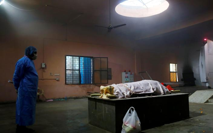 Alone in an empty room, a family member dressed head-to-toe in personal protective equipment waits with the body of their relative, a victim of Covid-19, before the cremation - REUTERS/Adnan Abidi