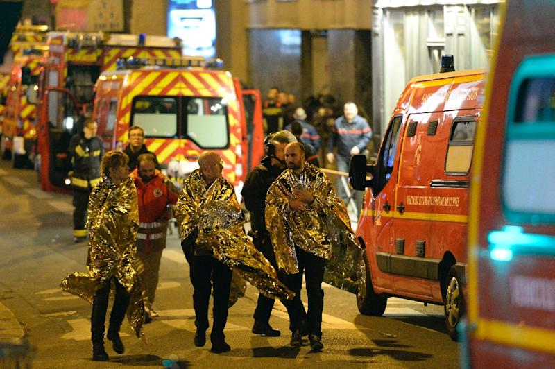 People are being evacuated on rue Oberkampf near the Bataclan concert hall in central Paris, early on November 14, 2015