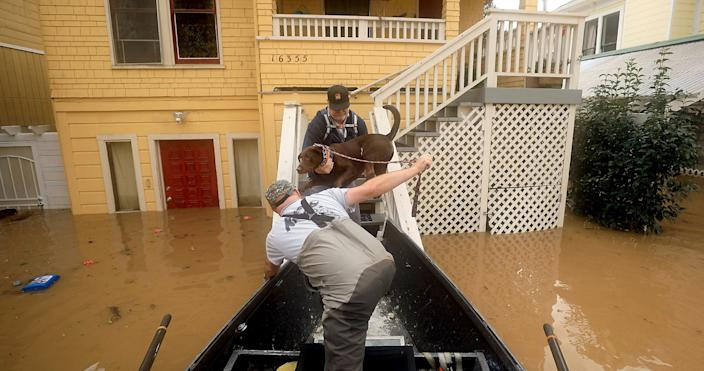 Scott Heemstra prepares to take David Youngberg and his dog Macallan out of the flood zone as floodwaters rise in Guerneville, Calif., Feb. 27, 2019. (Photo: Kent Porter/The Press Democrat via AP)