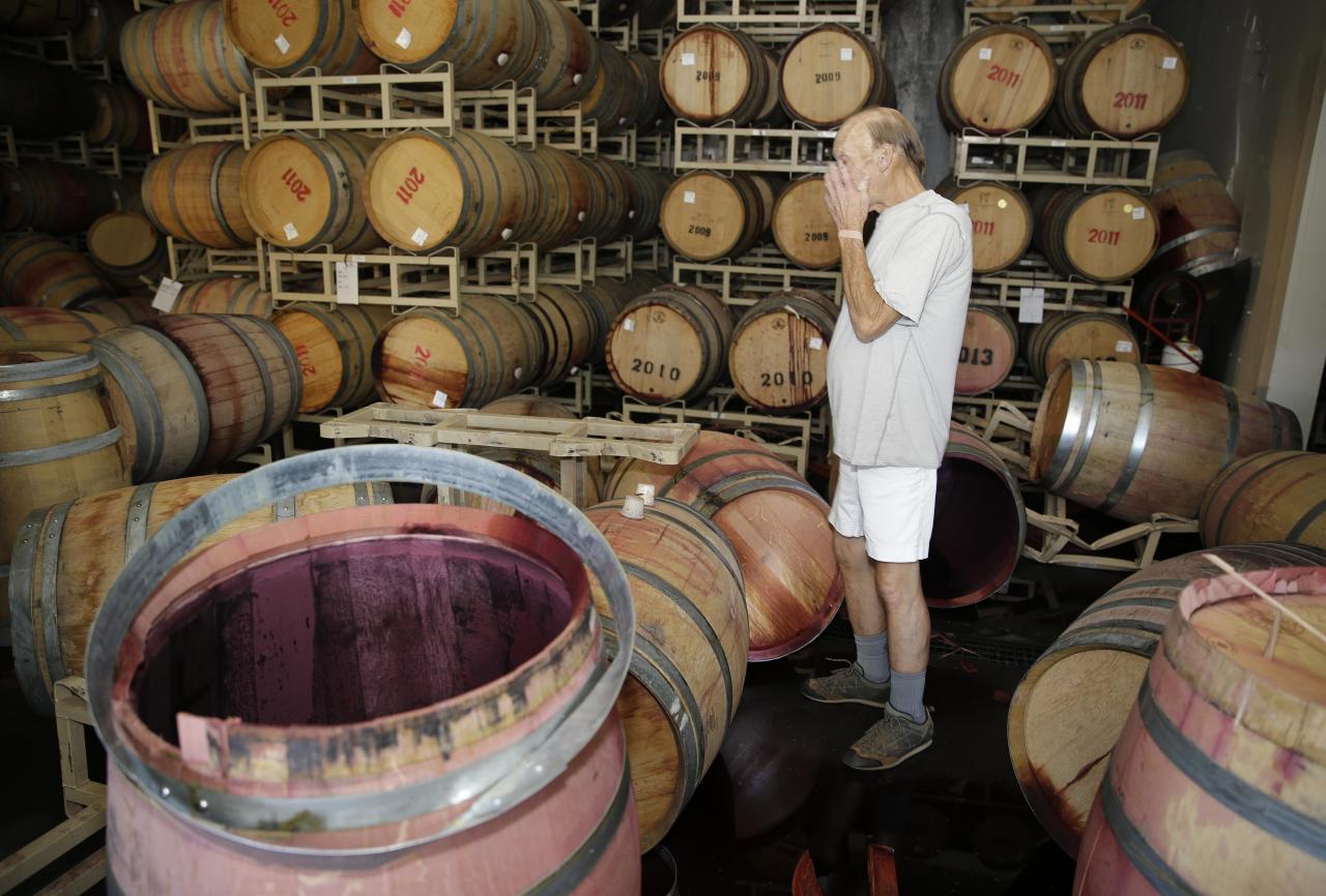 Winemaker Tom Montgomery stands in wine and reacts to seeing damage following an earthquake at the B.R. Cohn Winery barrel storage facility Sunday, Aug. 24, 2014, in Napa, Calif. Winemakers in California's storied Napa Valley woke up to thousands of broken bottles, barrels and gallons of ruined wine as a result of Sunday's earthquake. (AP Photo/Eric Risberg)