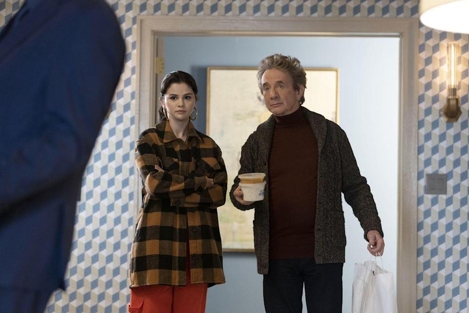 """<p>In an exclusive sneak peek at the upcoming fourth episode of Only Murders In The Building, Gomez wears orange cargo trousers from Urban Outfitters, an oversized brown and black plaid shirt by Aqua, and her trusty Jennifer Fisher gold earrings. </p><p><a class=""""link rapid-noclick-resp"""" href=""""https://go.redirectingat.com?id=127X1599956&url=https%3A%2F%2Fwww.net-a-porter.com%2Fen-gb%2Fshop%2Fproduct%2Fjennifer-fisher%2Fjewelry-and-watches%2Fearrings%2Fbaby-lilly-gold-plated-hoop-earrings%2F17957409490661424&sref=https%3A%2F%2Fwww.elle.com%2Fuk%2Ffashion%2Fcelebrity-style%2Fg37396246%2Fselena-gomez-only-murders-in-the-building%2F"""" rel=""""nofollow noopener"""" target=""""_blank"""" data-ylk=""""slk:SHOP NOW"""">SHOP NOW</a> Jennifer Fisher Baby Lilly gold-plated hoop earrings, £280</p><p><a class=""""link rapid-noclick-resp"""" href=""""https://go.redirectingat.com?id=127X1599956&url=https%3A%2F%2Fwww.urbanoutfitters.com%2Fen-gb%2Fshop%2Fbdg-y2k-red-cargo-trousers%3Fcategory%3Dwomens-trousers%26color%3D060%26type%3DREGULAR%26quantity%3D1&sref=https%3A%2F%2Fwww.elle.com%2Fuk%2Ffashion%2Fcelebrity-style%2Fg37396246%2Fselena-gomez-only-murders-in-the-building%2F"""" rel=""""nofollow noopener"""" target=""""_blank"""" data-ylk=""""slk:SHOP NOW"""">SHOP NOW</a> Urban Outfitters BDG Y2K Red Cargo Trousers,<br>£55.00<br></p>"""