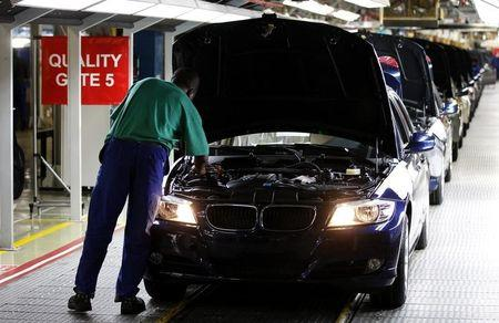 A worker inspects cars at BMW's manufacturing plant in Rosslyn, outside Pretoria