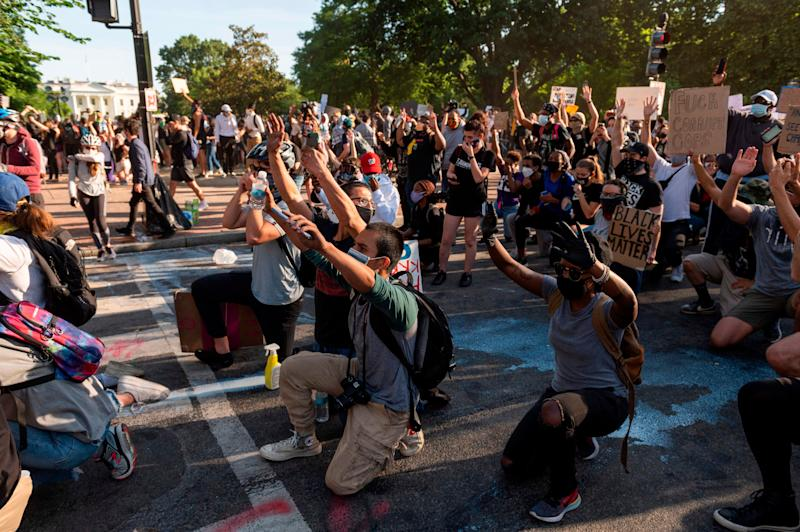 Protestors take a knee and raise their hands as they face riot police near the White House on June 1 as demonstrations against George Floyd's death continue. (Photo: ROBERTO SCHMIDT via Getty Images)