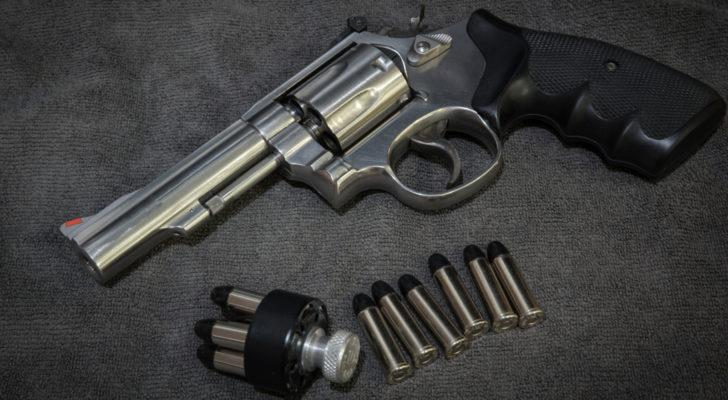 Image of a pistol and several bullets laying on a dark grey surface (cyclical stocks)