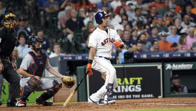 Houston Astros' Michael Brantley, right, hits a two-run double as Detroit Tigers catcher Jake Rogers, center, watches during the second inning of a baseball game Tuesday, Aug. 20, 2019, in Houston. (AP Photo/David J. Phillip)