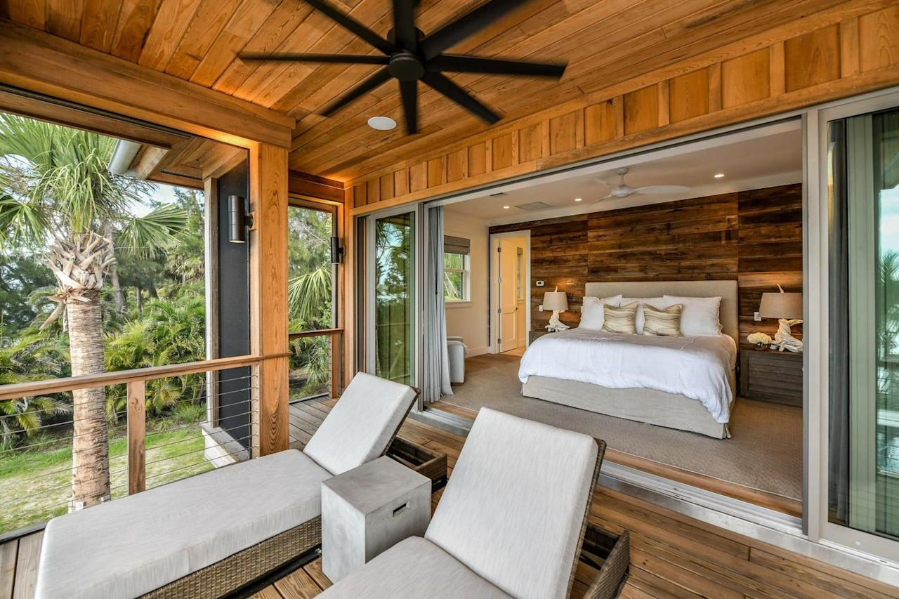 """<p>In this relaxed bedroom by <a href=""""https://www.chairish.com/shop/alene-workman-interior-design"""">Alene Workman Interior Design</a>, retractable sliding doors blend indoor and outdoor living. Full of raw woods, the tropical space has a cabin feel. </p>"""