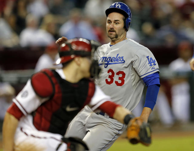 Los Angeles Dodgers' Scott Van Slyke (33) scores on a sacrifice fly by teammate Michael Young as Arizona Diamondbacks catcher Miguel Montero waits for the throw during the sixth inning of a baseball game on Thursday, Sept. 19, 2013, in Phoenix. (AP Photo/Matt York)