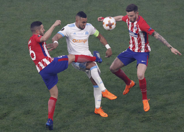 Marseille's Dimitri Payet, center, passes the ball despite Atletico's Koke, left, during the Europa League Final soccer match between Marseille and Atletico Madrid at the Stade de Lyon outside Lyon, France, Wednesday, May 16, 2018. (AP Photo/Christophe Ena)