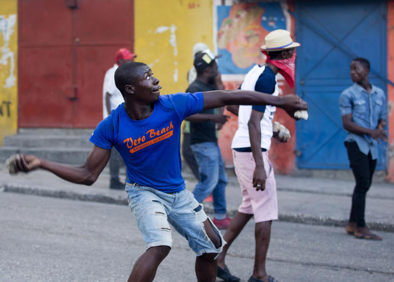 Demonstrators throw rocks at neighborhood locals during a protest to demand the resignation of Haiti's president Jovenel Moise on the 216th anniversary of Battle of Vertieres in Port-au-Prince, Haiti, Monday, Nov. 18, 2019. At least four people were shot and wounded during a small protest in Haiti's capital after a speech by embattled President Moise. A local journalist, a police officer and two protesters were rushed away with apparent bullet wounds. (AP Photo/Dieu Nalio Chery)
