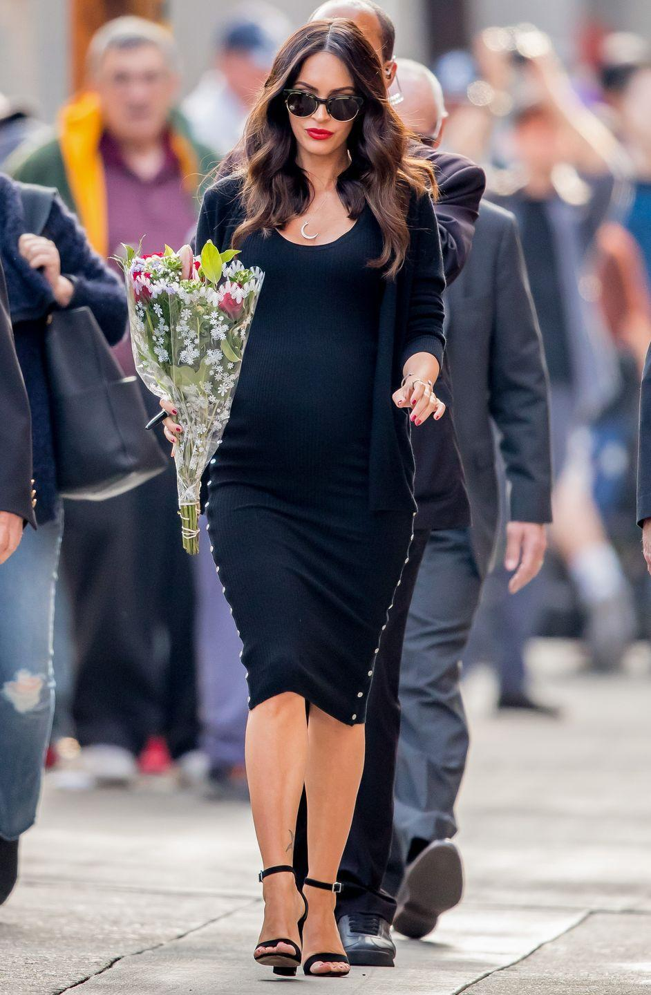 <p>Fox styled her pregnancy bump in a black knitted midi dress, black heels and a black knitted cardigan. She accessorised the look with a bunch of flowers, a red lip and sunglasses. </p>
