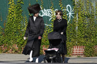 An Ultra-Orthodox man and woman cross a street, Sunday, Oct. 4, 2020, in the Borough Park neighborhood of New York on the Jewish holiday of Sukkot. Over the past two weeks, the number of new cases of coronavirus has been rising in pockets of the city, predominantly in neighborhoods in Queens and Brooklyn, including Borough Park, that are home to the city's large Orthodox Jewish population. (AP Photo/Kathy Willens)