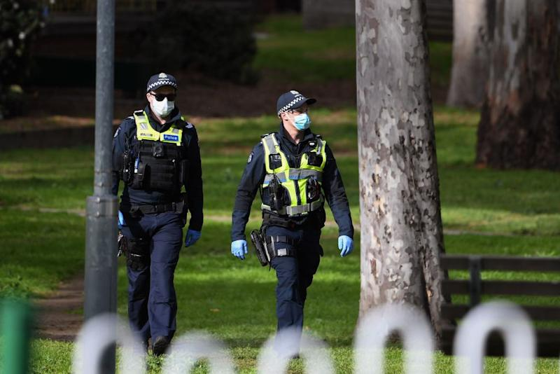 Police patrol the grounds of a public housing estate which is undergoing a forced lockdown in Melbourne.