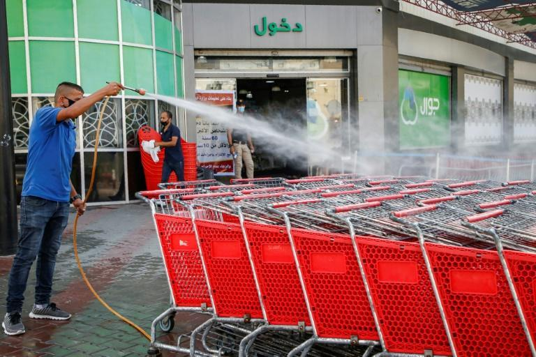 A mask-clad Palestinian worker disinfects supermarket carts