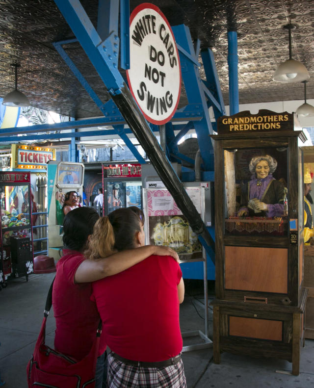"""This June 12, 2013 photo shows a couple looking at the 90-year-old fortune telling machine """"Grandma's Predictions,"""" which was restored after damage in superstorm Sandy at the amusement park in the Coney Island neighborhood in the Brooklyn borough of New York. (AP Photo/Bebeto Matthews)"""
