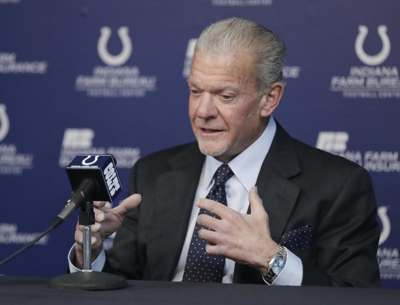 Jim Irsay talks at a podium with Colts logos.