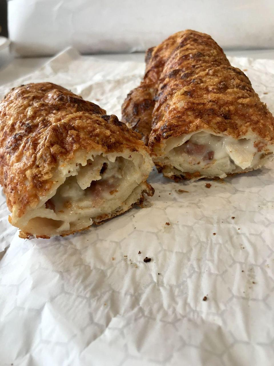 <p>The chicken bake is basically a glorified Hot Pocket—if a Hot Pocket were twice as long and way fluffier. It tastes like a croissant with crispy asiago cheese on top, and I am HERE for it. </p><p>Inside, there's chicken breast, cheese, bacon, and caesar dressing, which is a fairly random but decidedly delicious combo. Come hungry for this one or plan to split it with your Costco buddy, because it's HUGE. </p>