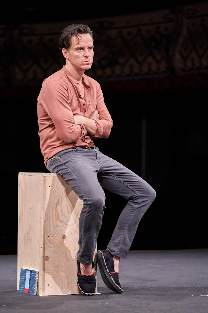 """Andrew Scott sits on a wooden box in the play """"Three Kings."""""""