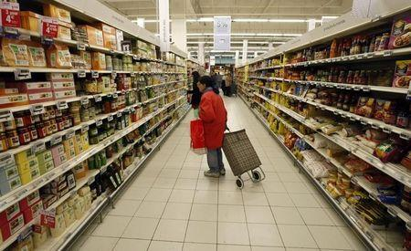 A woman looks at a food department in a super market in Nice