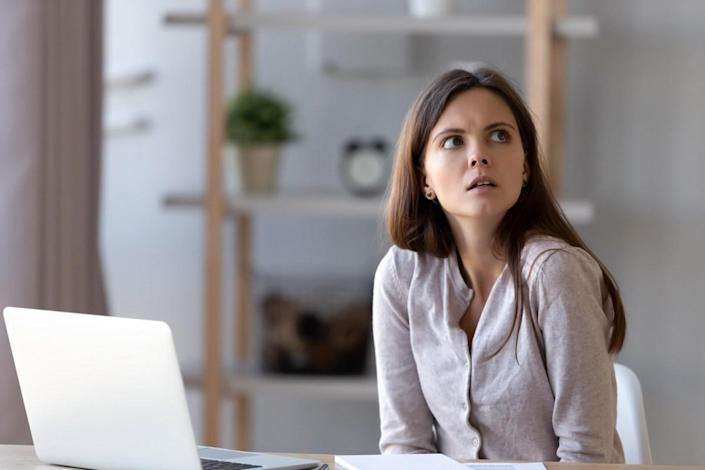 Confused young woman sit at office home desk working at laptop