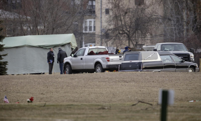 Workers at Rosehill Cemetery in Chicago on Friday, Jan. 18, 2013, begin the process of exhuming the body of Urooj Khan who was poisoned with cyanide after winning the lottery. Khan died in July as he was about to collect $425,000 in lottery winnings. His death was initially ruled a result of natural causes, but a relative pressed for a deeper look and his death was reclassified as a homicide. (AP Photo/M. Spencer Green)