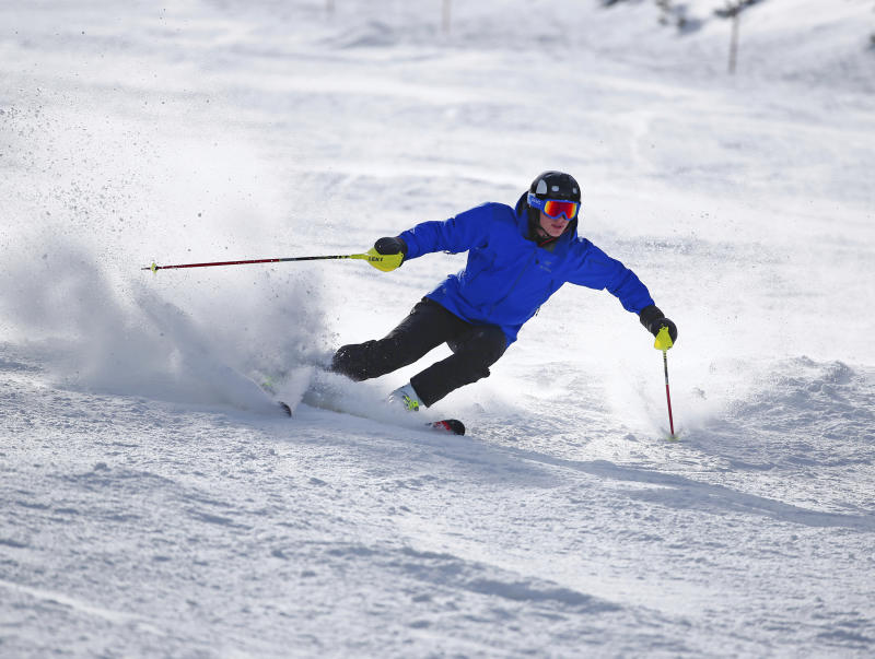 FILE - In this Oct. 29, 2015, file photo, a skier kicks up some fresh powder during opening day at Arapahoe Basin in Dillon, Colo. If you're contemplating a ski vacation this winter, the best deals and discounts typically are offered well before winter. Some options sell out altogether as ski season approaches, especially nonstop flights and stays at ski-in, ski-out properties. (AP Photo/Jack Dempsey, File)