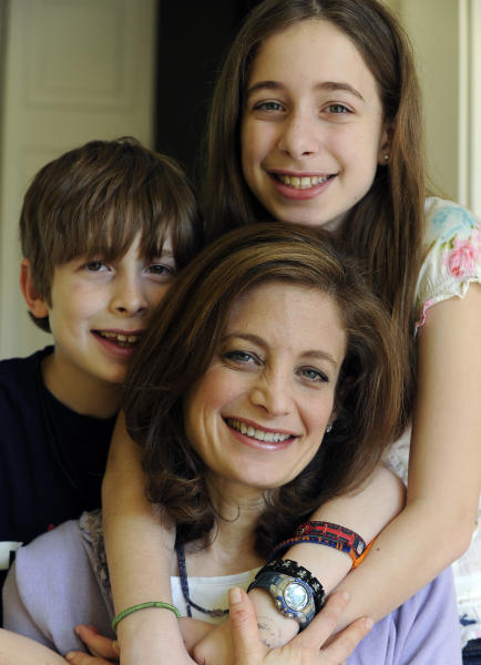 "In this March 12, 2012 photo, Bettina Siegel, center, poses with her son Asher, 9, and daughter Lily, 12, at their home in Houston. Siegel, whose blog ""The Lunch Tray"" focuses on kids' food, was so upset over a report of ammonia-treated meat trimmings in school lunches she started an online petition asking Agriculture Secretary Tom Vilsack to ""put an immediate end to the use of 'pink slime' in our children's school food."" As of Monday she had more than 175,000 online signatures. (AP Photo/Pat Sullivan)"