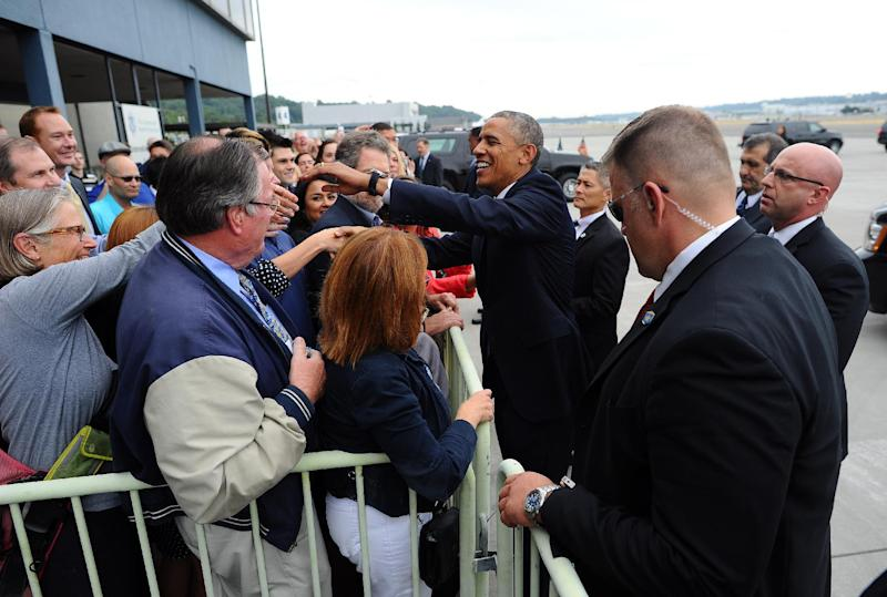 US President Barack Obama greets a group of people upon arriving at Boeing Field / King County International Airport in Seattle, Washington, on July 22, 2014