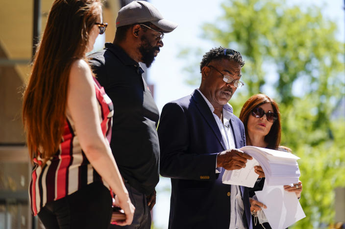 From left, Brooke Vaughn, her husband former NFL player Clarence Vaughn III, former NFL player Ken Jenkins and his wife Amy Lewis read a letter before delivering tens of thousands of petitions demanding equal treatment for everyone involved in the settlement of concussion claims against the NFL, to the federal courthouse in Philadelphia, Friday, May 14, 2021. (AP Photo/Matt Rourke)