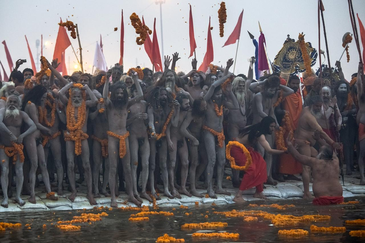 ALLAHABAD, INDIA - JANUARY 14:  (EDITORS NOTE: Image contains nudity.) Naga sadhus line up along the banks of Sangam, the confluence of the holy Ganges and Yamuna rivers during the auspicious bathing day of Makar Sankranti , the start of the Maha Kumbh Mela on January 14, 2013 in Allahabad, India. The Maha Kumbh Mela, believed to be the largest religious gathering on earth is held every 12 years on the banks of Sangam, the confluence of the holy rivers Ganga, Yamuna and the mythical Saraswati. The Kumbh Mela alternates between the cities of Nasik, Allahabad, Ujjain and Haridwar every three years. The Maha Kumbh Mela celebrated at the holy site of Sangam in Allahabad, is the largest and holiest, celebrated over 55 days, it is expected to attract over 100 million people. (Photo by Daniel Berehulak/Getty Images)