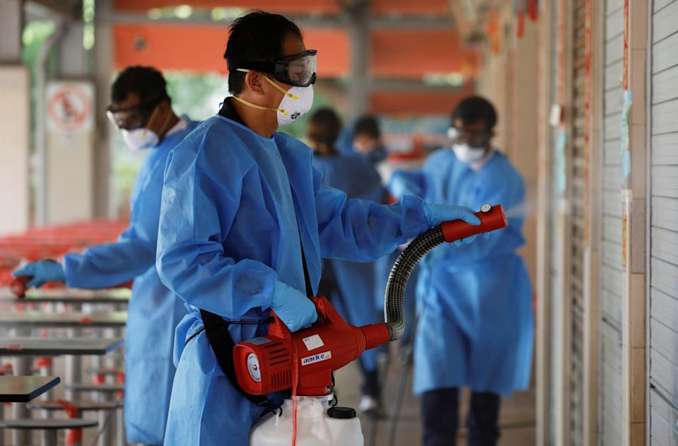 Cleaners disinfect a food center that was closed down after a hawker tested positive for the coronavirus disease (COVID-19), in Singapore, June 16, 2021. REUTERS/Edgar Su
