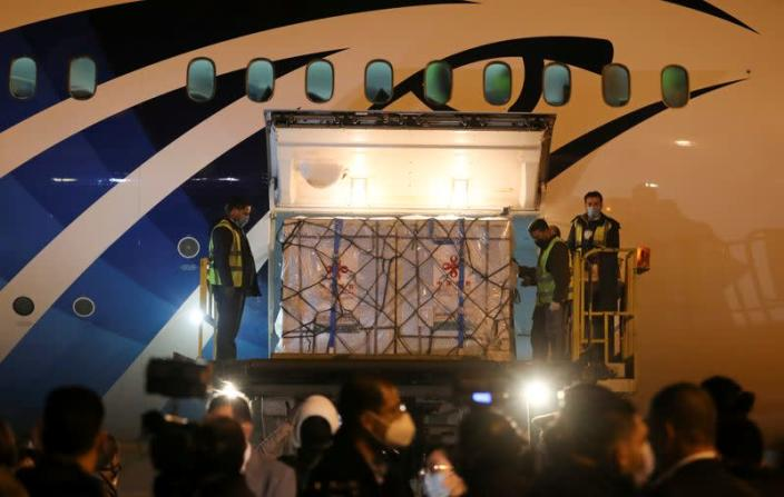 """FILE PHOTO: Workers offload pallets containing coronavirus disease (COVID-19) vaccine """"Sinopharm"""" doses as they arrive from China at Cairo International Airport amid the coronavirus disease (COVID-19) pandemic in Cairo"""