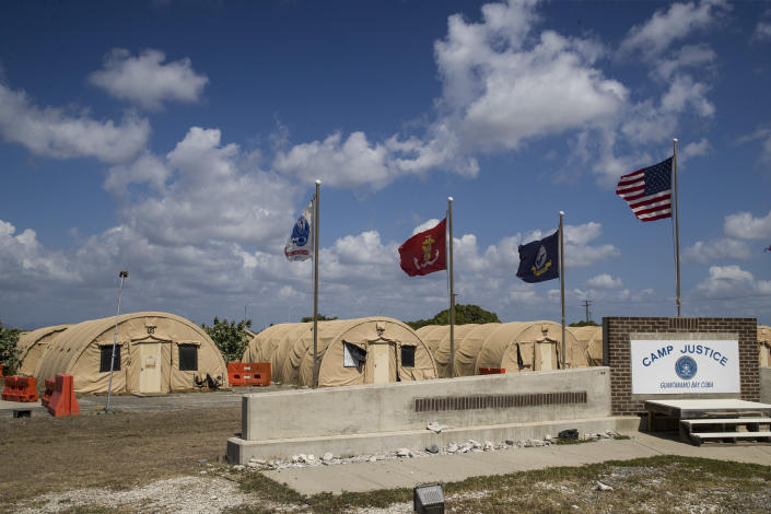 FILE - In this April 18, 2019, file photo, in this photo reviewed by U.S. military officials, flags fly in front of the tents of Camp Justice in Guantanamo Bay Naval Base, Cuba. A plan to offer the COVID-19 vaccine to prisoners at the Guantanamo Bay detention center, which was halted earlier in 2021 amid a political backlash, is on again as health authorities on April 19, 2021 expanded the vaccination program on the Navy base in Cuba to the entire adult population of the remote facility (AP Photo/Alex Brandon, File)