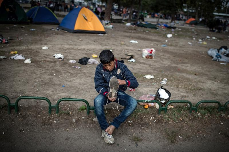 A boy checks his shoe at a park where migrants have found temporary shelter in the Serbian capital Belgrade on August 25, 2015 (AFP Photo/Andrej Isakovic)