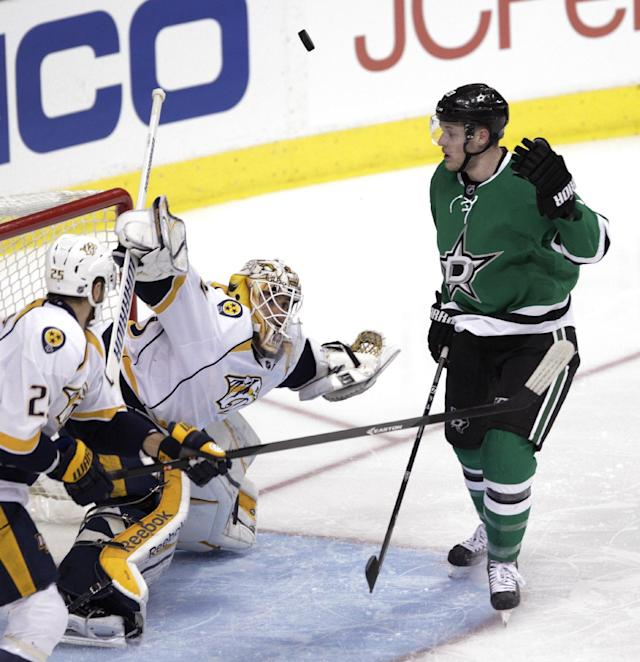 Dallas Stars defenseman Kevin Connauton (23) attempts to toss the puck into the net as Nashville Predators goalie Carter Hutton (30) defends while Nashville Predators left wing Viktor Stalberg (25) watches during the first period of an NHL hockey game Friday, Dec. 27, 2013, in Dallas. (AP Photo/Tim Sharp)