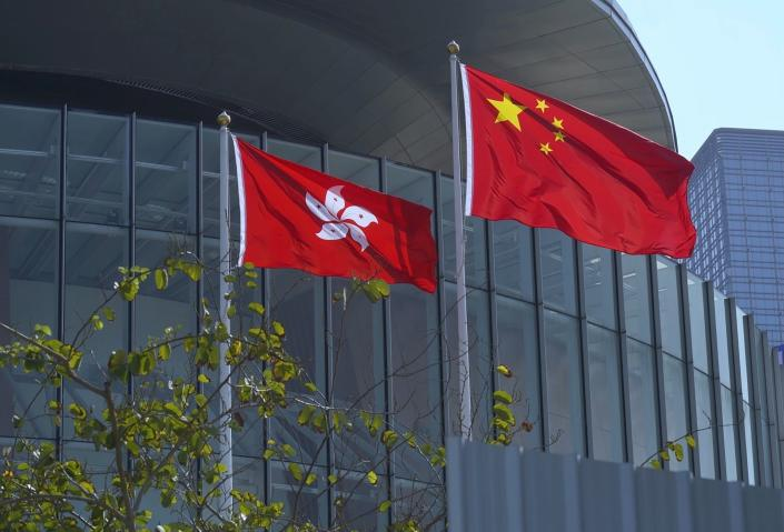 """FILE - In this April 13, 2021, file photo, China's national flag, right, and Hong Kong's flag flutter at the Legislative Council in Hong Kong. Hong Kong's polls for an election committee that will vote for the city's leader kicked off Sunday amid heavy police presence, with chief executive Carrie Lam saying that it is """"very meaningful"""" as it is the first election to take place following electoral reforms. (AP Photo/Vincent Yu, File)"""