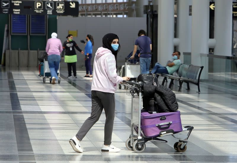 A passenger wearing a protective face mask pushes a trolley at Beirut international airport