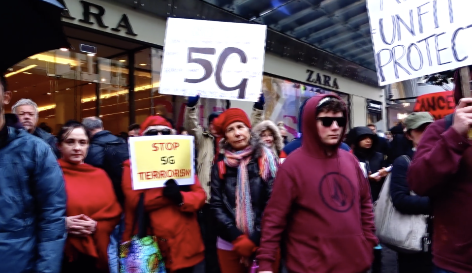 5G protestors in Melbourne are pictured holding signs that read 'Stop 5G terrorism' and demanding protection.