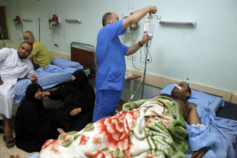 Victims are treated in a local hospital after a car bomb attack in Baghdad, Iraq, Friday, Aug. 17, 2012. Iraqi officials said Friday that a blistering string of attacks across the country the previous day ultimately killed scores of people, as the extent of the violence grew clearer and mourners started to bury their dead.(AP Photo/Karim Kadim)