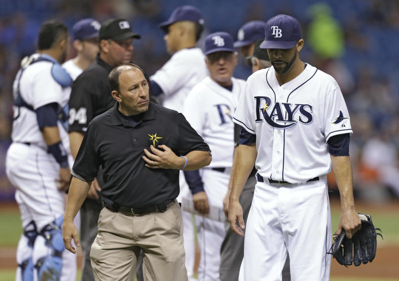 Tampa Bay Rays trainer Ron Porterfield, left, looks at starting pitcher David Price, right, as he leaves the baseball game with an injury during the third inning against the Boston Red Sox, Wednesday, May 15, 2013, in St. Petersburg, Fla. (AP Photo/Chris O'Meara)